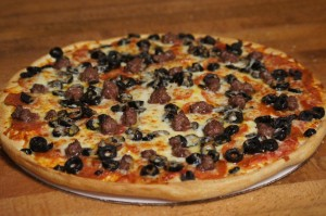 large pepperoni meatball and black olives pizza