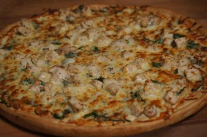 white pizza with chicken and fresh spinach